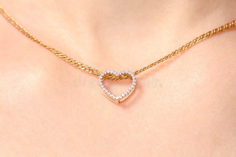 妇女在脖子金链子垂饰心脏的` s首饰 免版税库存图片