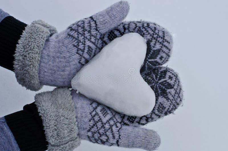 妇女在舒适温暖的手套的` s手保留心脏在雪外面以雪为背景 免版税库存照片