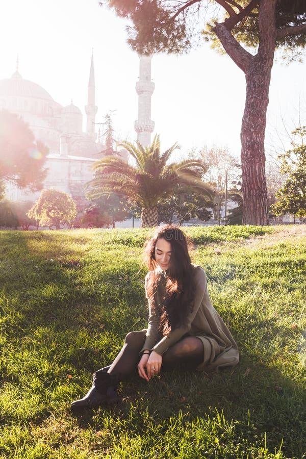 妇女在草放松靠近蓝色清真寺在好日子 库存照片