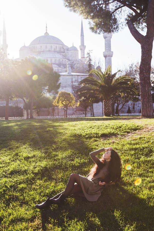 妇女在草放松靠近蓝色清真寺在好日子 免版税库存图片