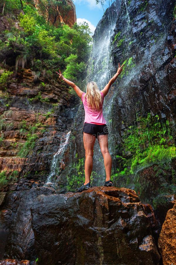 妇女在落下的瀑布前面的岩石站立 免版税库存照片