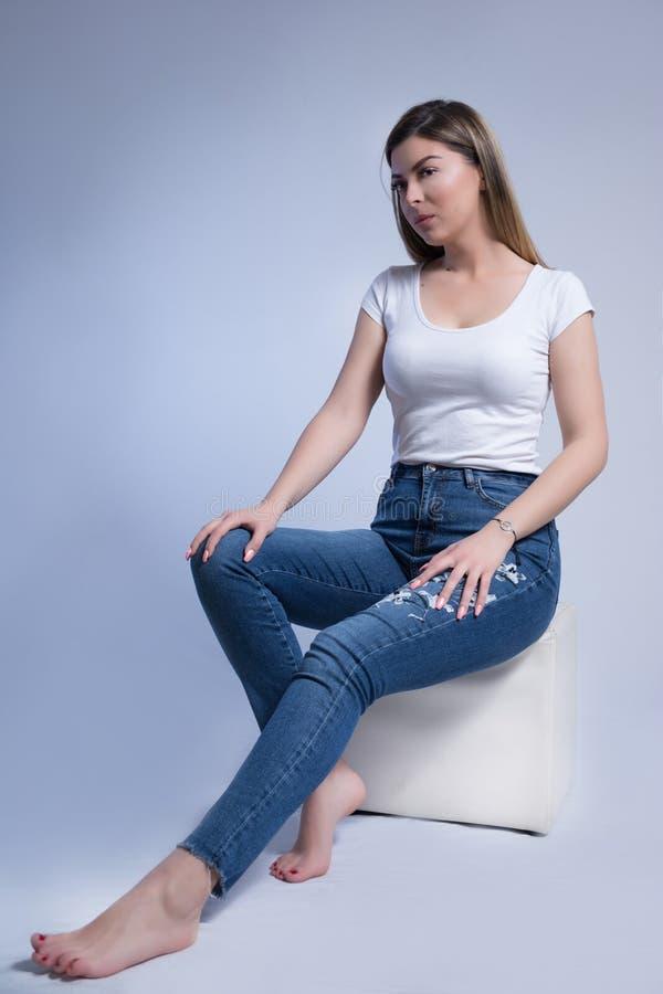 妇女在蓝色牛仔裤和赤脚坐被隔绝白色立方体的凳子在演播室和在白色蓝色背景 库存图片