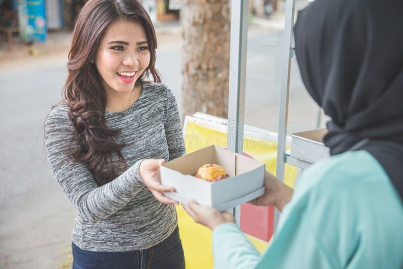 妇女在街道食物摊位的购买蛋糕 库存图片