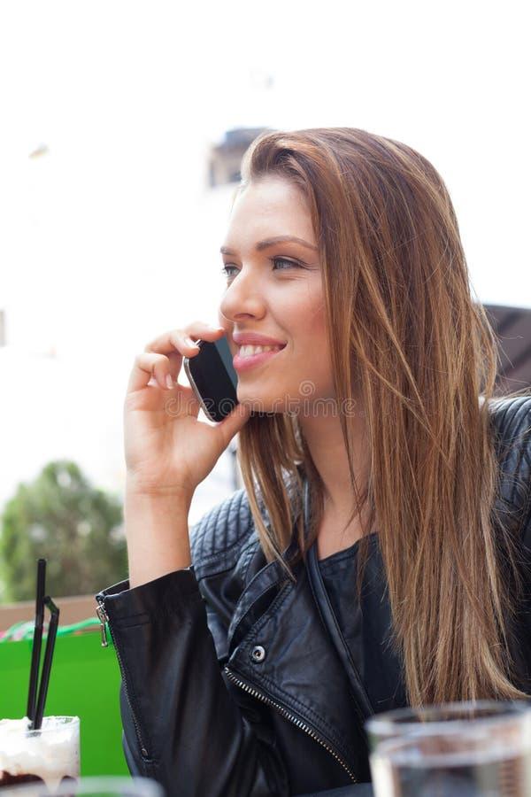 妇女在谈话的桌上坐电话 免版税库存照片