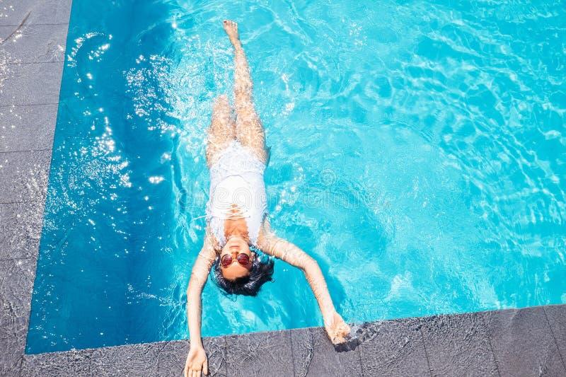 妇女在豪华旅游胜地的游泳池放松 库存图片