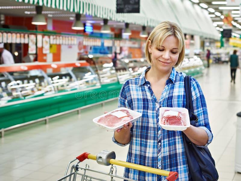 妇女在超级市场买肉 免版税图库摄影