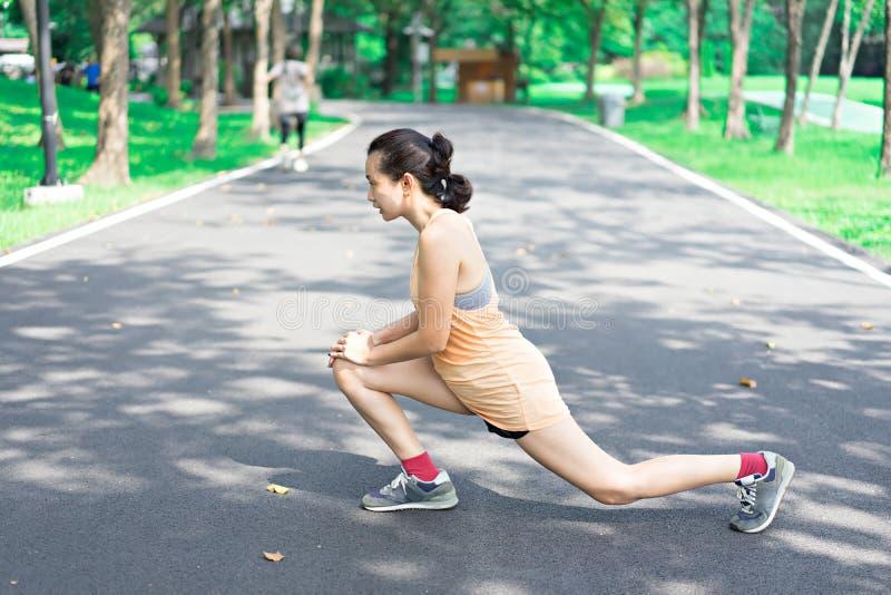 妇女在跑步前舒展在公园 免版税库存图片