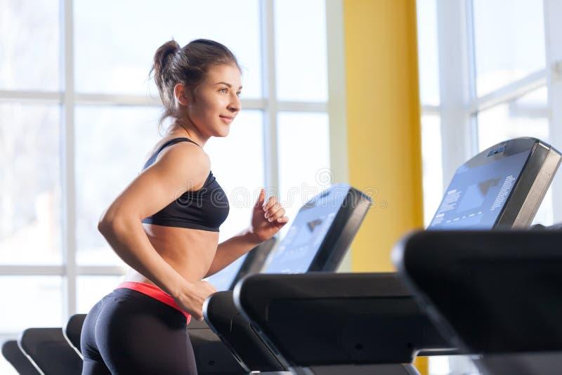 妇女在踏车跑在健身房 图库摄影