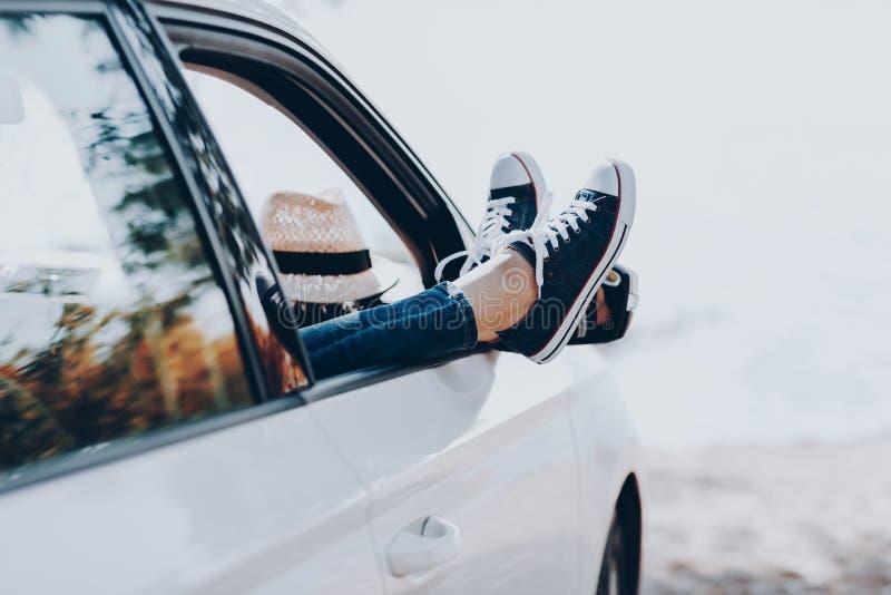 妇女在运动鞋的` s腿在有草帽的窗口汽车 牛仔裤的女孩在有她的盘的腿的汽车 免版税库存照片