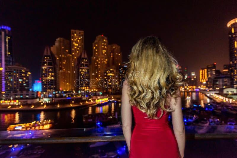 妇女在迪拜小游艇船坞,阿拉伯联合酋长国 穿一件红色礼服的可爱的夫人 敬佩小游艇船坞视图的女孩在晚上 库存图片