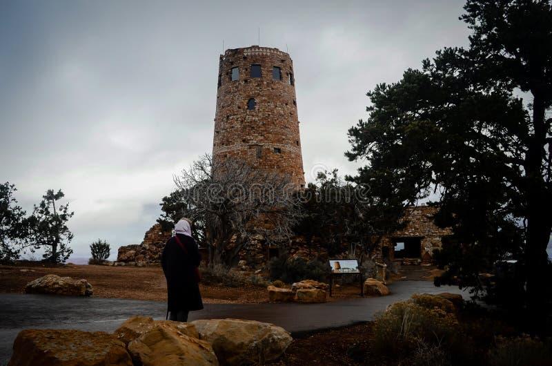 妇女在道路停留观察手表塔在大峡谷在一冷的刮大风天 免版税库存图片
