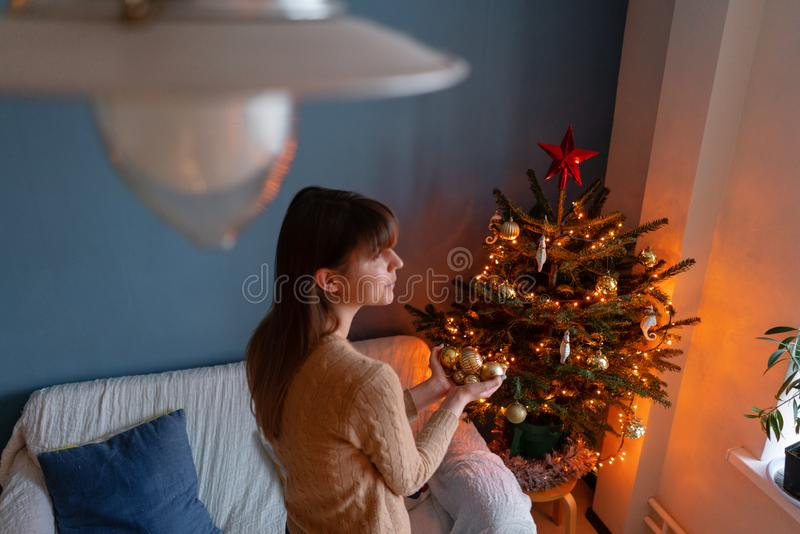 妇女在金黄圣诞树玩具的手上举行 在房子内部的寒假 金黄和白色圣诞节快乐 免版税库存照片