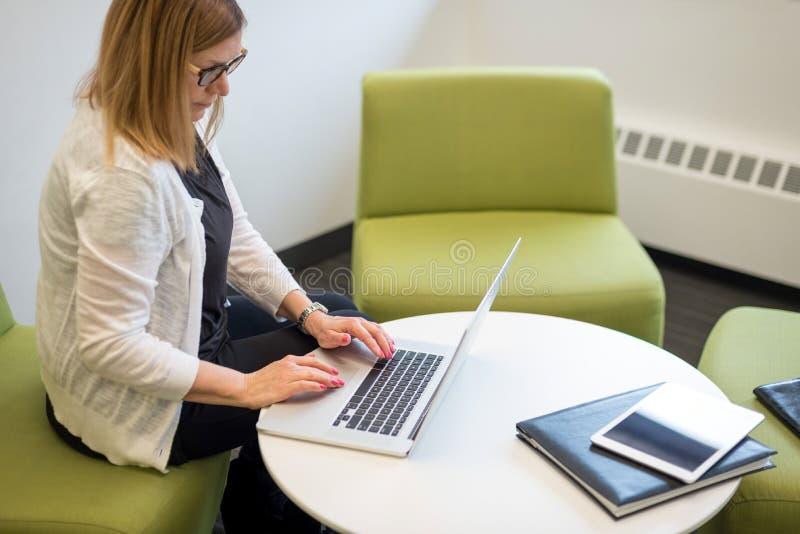 妇女在键入现代的工作区坐便携式计算机 免版税库存照片