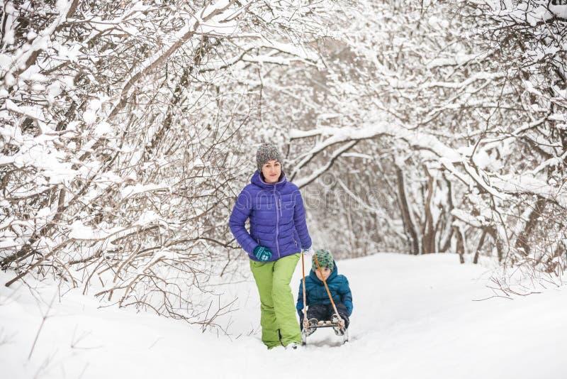 妇女在雪撬滚动男孩 免版税库存图片