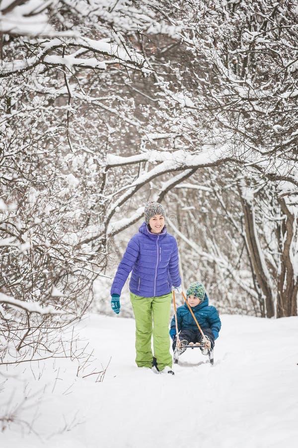 妇女在雪撬滚动男孩 免版税库存照片