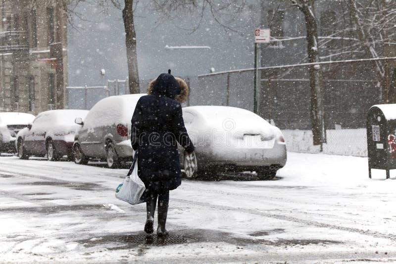 妇女在雪风暴期间的横穿街道 库存图片