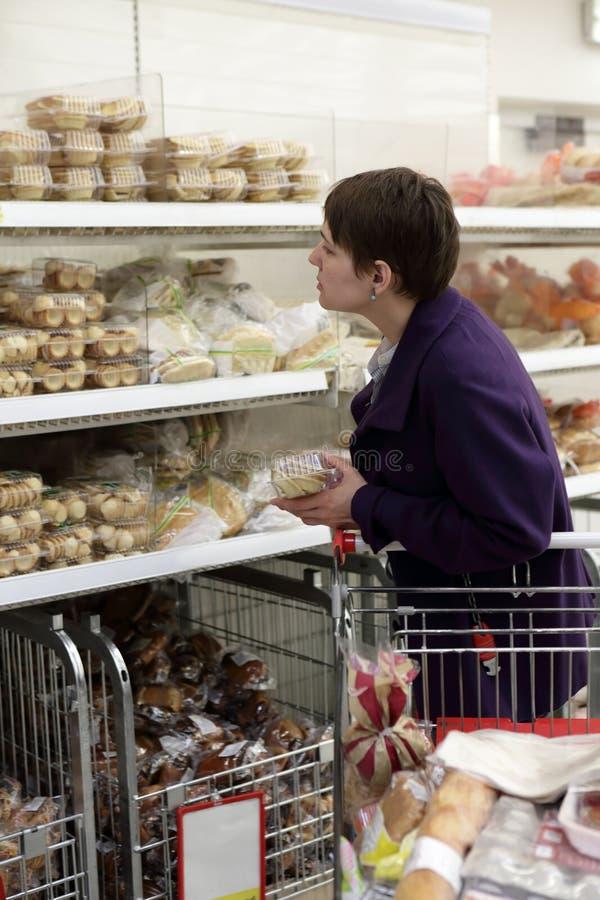 妇女在面包店商店 库存照片