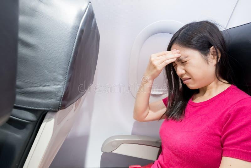 妇女在飞机的感受头疼 免版税库存照片