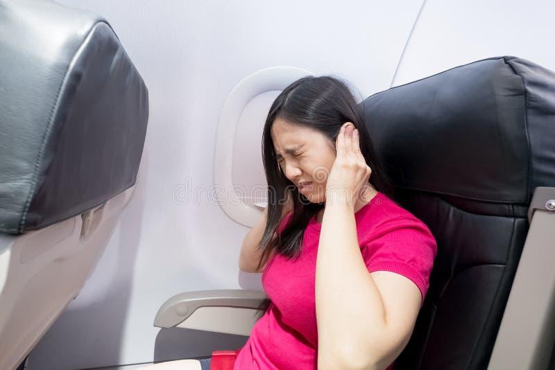妇女在飞机的感受耳鸣 库存图片
