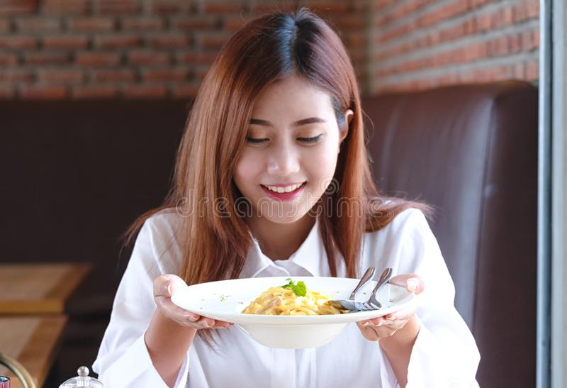 妇女在餐馆享用她的意粉 库存图片