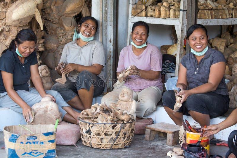 妇女在巴厘岛做游人的木纪念品 免版税库存照片