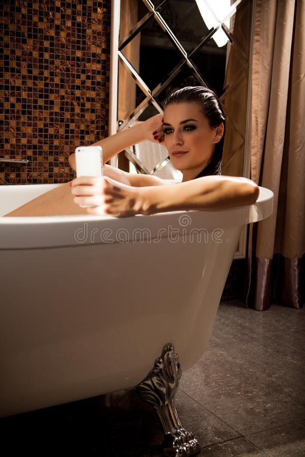 妇女在浴坐并且有videochat由智能手机 免版税库存图片