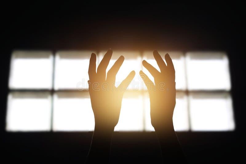 妇女在黑暗的背景的屋子里递祈祷保佑的从神 库存照片