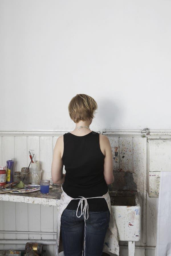 妇女在水槽的清洁油漆刷 免版税库存图片