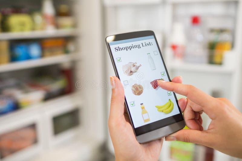 妇女在他的智能手机做她的购物单被连接到冰箱 库存图片