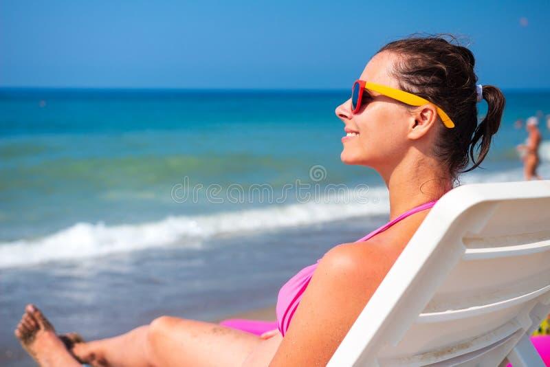 妇女在deckchair放松反对蓝色海水 库存图片