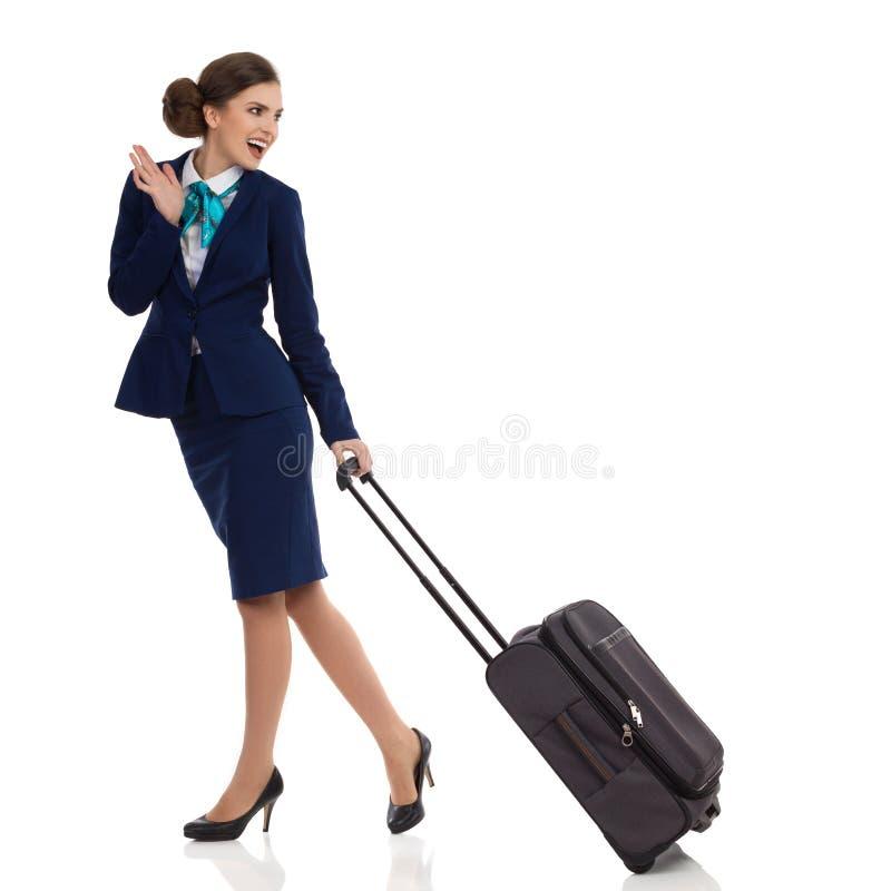 妇女在Formalwear走与台车袋子和挥动 库存照片
