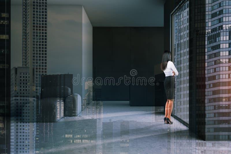 妇女在minimalistic灰色客厅 库存照片