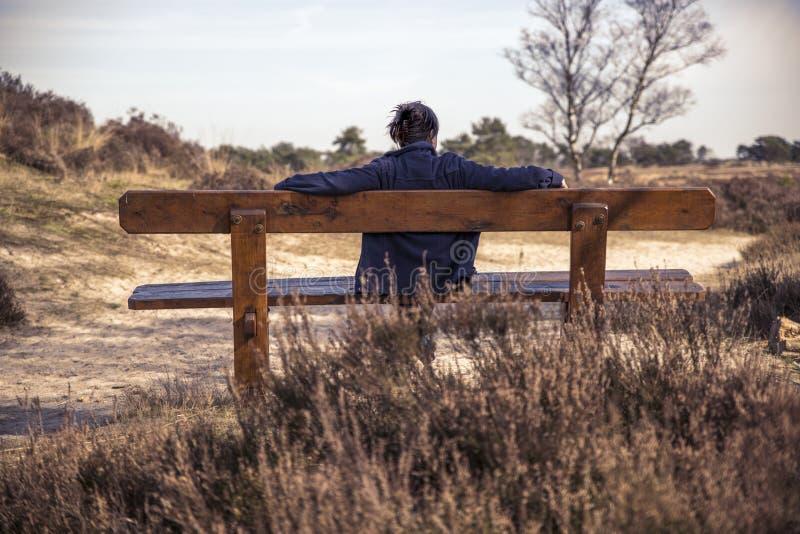 妇女坐一条长凳本质上 免版税图库摄影