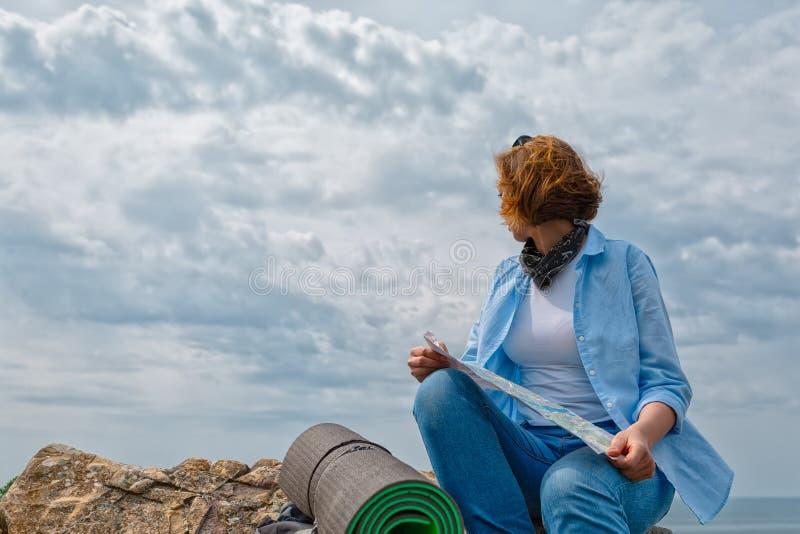 妇女坐与一张地图的小山在她的手上 在背景中,与云彩的天空 ?? 库存照片