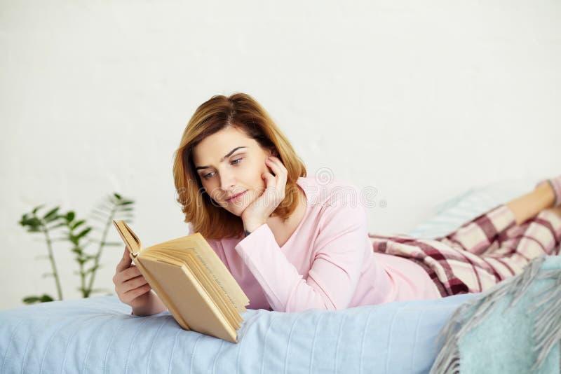 妇女坐与书的床 免版税图库摄影
