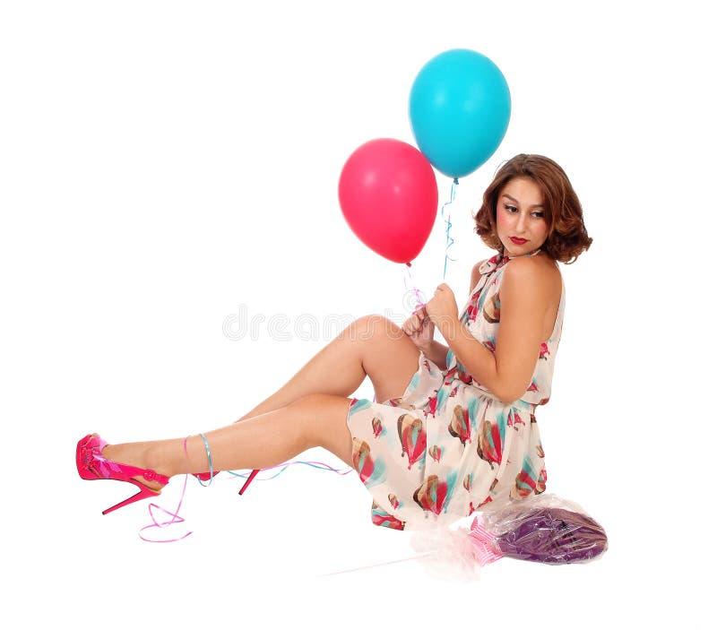妇女坐与气球的地板 免版税图库摄影