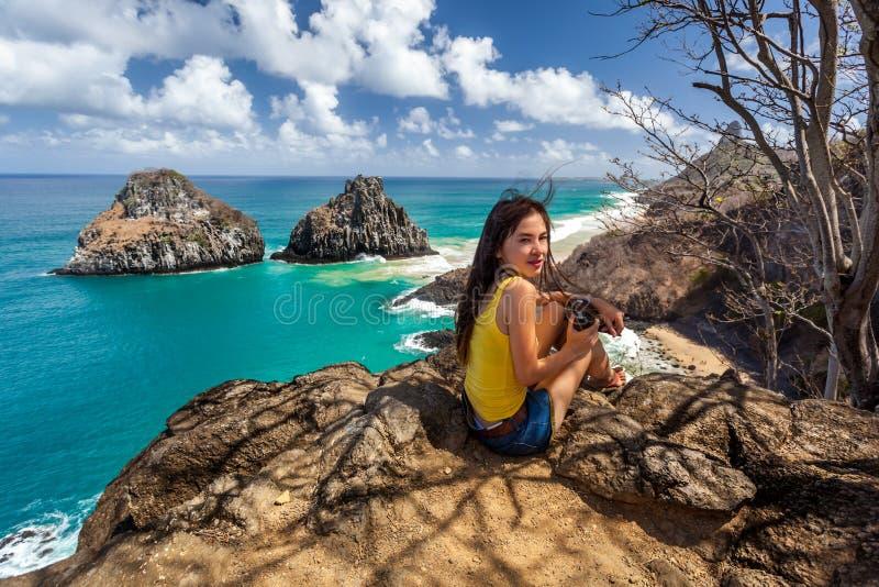 妇女坐与照相机在两个兄弟岩石,费尔南多・迪诺罗尼亚群岛附近 免版税图库摄影