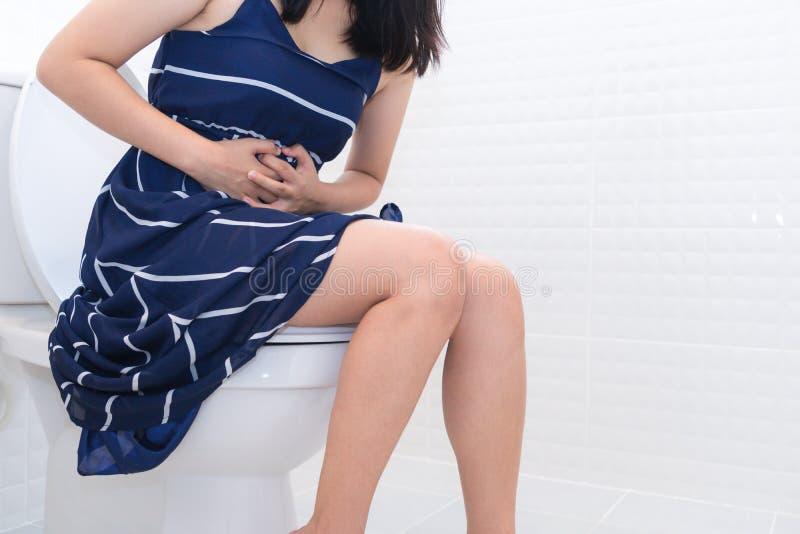 妇女坐与腹泻或便秘症的痛苦concep的洗手间 免版税库存照片