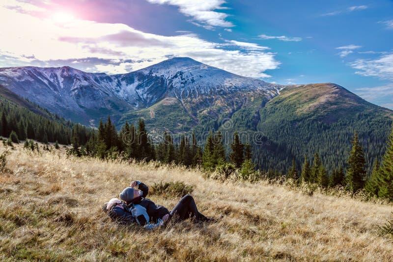 妇女坐享受温暖的阳光的黄色象草的草甸 免版税库存图片