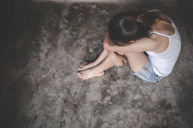 妇女坐单独台阶有消沉、家庭问题、厨房、恶习和人概念的 库存照片
