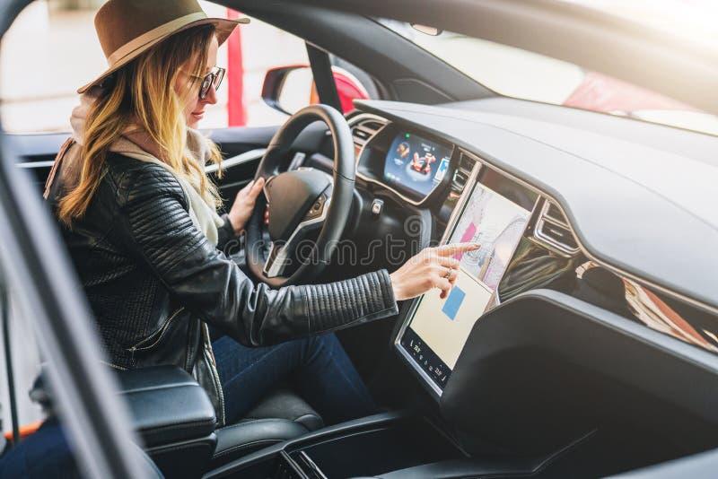 妇女坐后边把汽车和用途电子仪表板引入 寻找方式的女孩旅客通过导航系统 库存图片