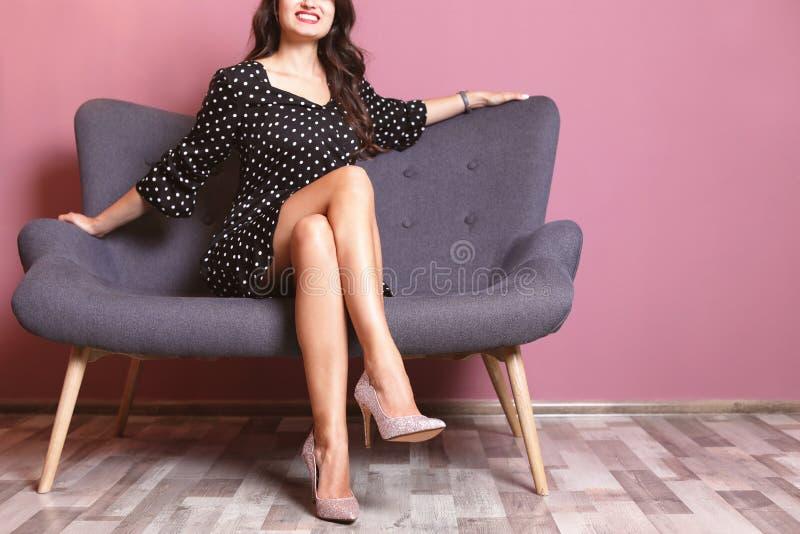 妇女坐在典雅的鞋子的沙发临近颜色墙壁 库存图片