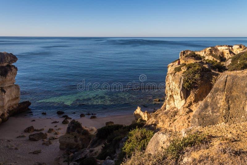 妇女坐在大西洋的岩石 库存照片