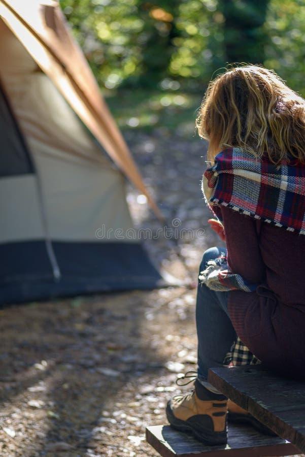 妇女坐在帐篷之外的野餐桌在露营地及早 库存图片
