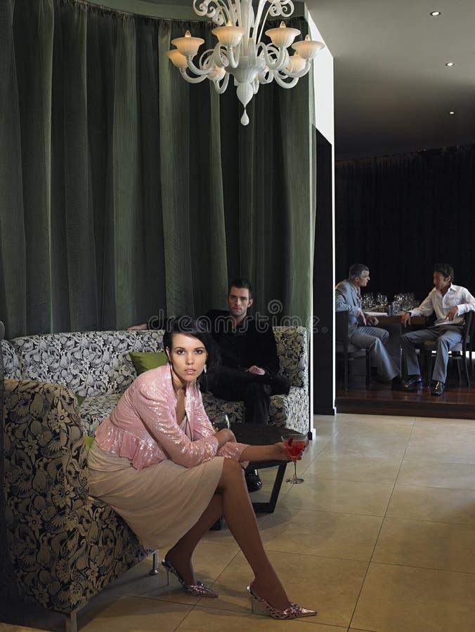 妇女坐在旅馆大厅的长沙发 免版税图库摄影