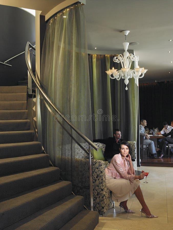 妇女坐在旅馆大厅的长沙发 库存照片