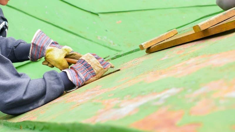 妇女坐在梯子旁边的,刮的油漆 库存图片