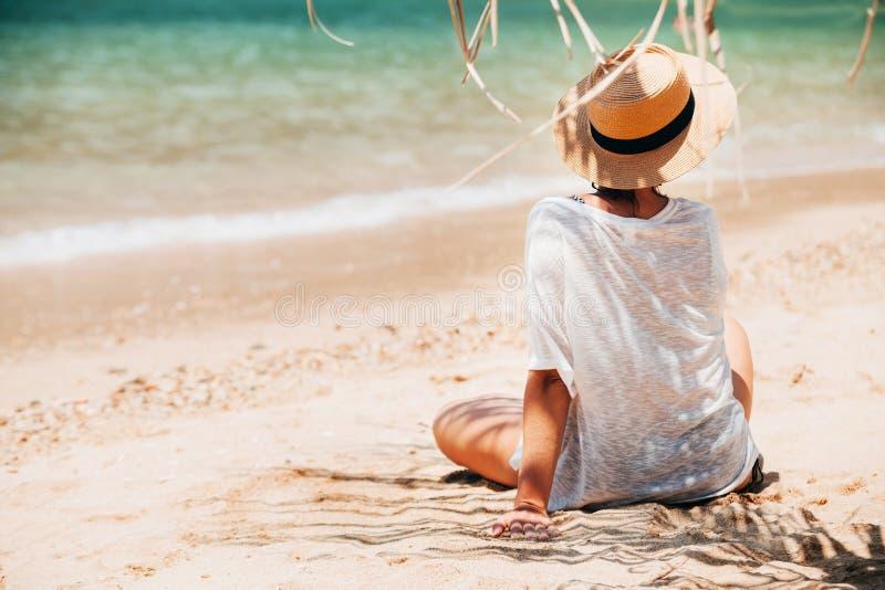 妇女坐在棕榈树阴影的海海滩 安全晒黑的概念 免版税图库摄影