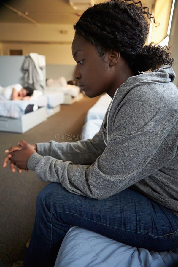妇女坐在流浪者避身处的床 库存照片