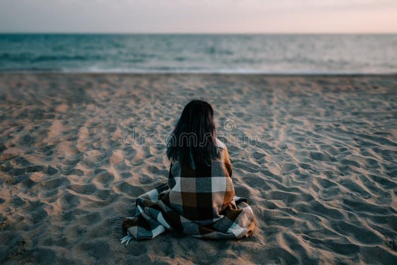 妇女坐在海前面的沙滩 库存图片